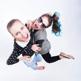 做滑稽的面孔-在蓝蓝背景的两个女孩 免版税库存照片