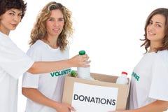 投入食物的志愿妇女在捐赠箱子 免版税图库摄影