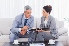 严肃的商人和谈话在沙发 免版税库存照片