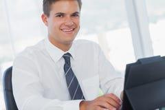 工作在他的片剂个人计算机的微笑的年轻商人 图库摄影