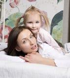 愉快的家庭、母亲和女儿画象床阅读书的 免版税库存照片