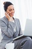 微笑的女实业家叫与她的手机和使用膝上型计算机坐沙发 免版税图库摄影