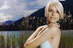 湖的美丽的现代白肤金发的妇女 免版税库存照片