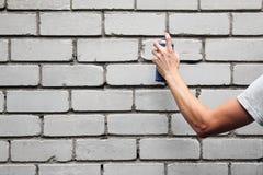 递拿着在墙壁前面的一个街道画喷壶 免版税库存照片