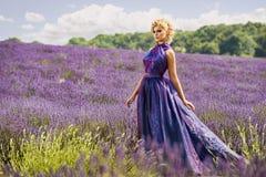 淡紫色领域的美丽的妇女 免版税库存图片