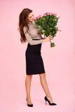 嗅到一束玫瑰的妇女 免版税库存图片