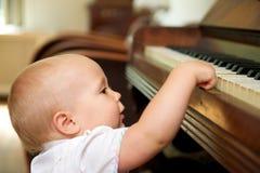 使用在钢琴的逗人喜爱的婴孩 免版税库存图片
