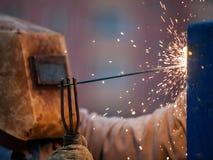 弧焊工工作者在防毒面具焊接金属建筑 免版税库存照片