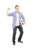 拿着球的一个欣快体育迷的全长画象 免版税库存图片