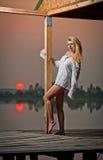 有一件白色衬衣的美丽的女孩在日落的码头 免版税库存图片