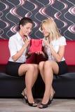 俏丽的女孩坐有礼物的红色沙发 免版税库存图片