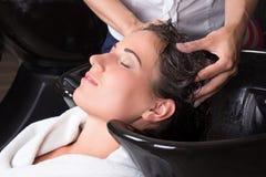 得到在沙龙的年轻可爱的妇女一次头发洗涤 免版税图库摄影