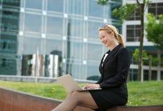 有膝上型计算机的愉快的女商人在办公室外 免版税库存图片