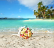玫瑰婚礼花束在一个热带海滩的岸的在的 免版税库存照片