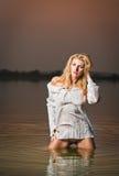 白色女衬衫的性感的白肤金发的妇女在河水 免版税库存图片