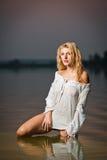 白色女衬衫的性感的白肤金发的妇女在河水 库存图片