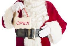 拿着开放标志的圣诞老人的中央部位 图库摄影