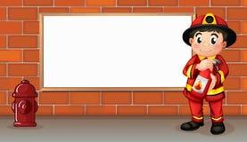有灭火器的一位消防员在一个空的委员会前面 免版税库存图片