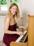 美丽白肤金发在家弹钢琴 库存图片
