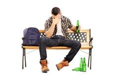 醉酒的男性少年坐长凳和饮用的啤酒 免版税库存照片
