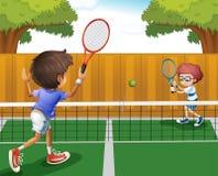 打在篱芭里面的两个男孩网球 免版税库存图片
