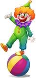 站立在球上的小丑 免版税库存照片