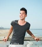 微笑对海滩的一个可爱的年轻人的画象 图库摄影