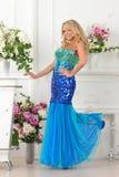 蓝色礼服的美丽的妇女在豪华内部。 免版税库存照片