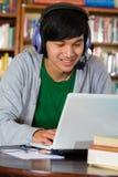 人在有膝上型计算机和耳机的图书馆里 免版税图库摄影