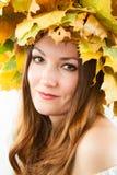 美丽的秋天妇女。女孩画象有槭树秋天花圈的在隔绝的头离开 免版税库存照片