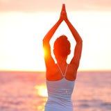 凝思思考在海滩日落的瑜伽妇女 库存照片