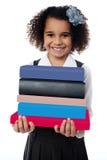 逗人喜爱的学校女孩运载的堆书 免版税库存照片