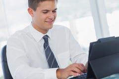 工作在他的片剂个人计算机的快乐的年轻商人 库存照片