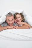 快乐的中部在鸭绒垫子下的年迈的夫妇 库存图片