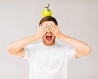人用在他的头的绿色苹果 库存图片