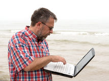 年长商人与笔记本坐海滩 库存图片