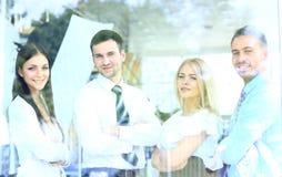 看通过窗口的微笑的企业队 免版税库存图片