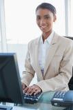 研究她的计算机的快乐的女实业家 免版税库存照片