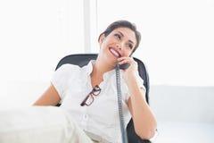 斜倚的女实业家在谈话她的书桌坐电话 免版税库存图片