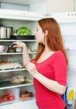 寻找某事在冰箱的红发妇女 免版税库存照片