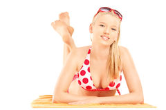 微笑的白肤金发女性说谎在海滩毛巾和看照相机 免版税库存照片