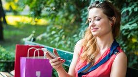 年轻愉快的妇女坐与五颜六色的购物袋和手机的一条长凳。 免版税库存照片