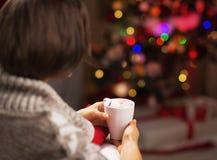 有巧克力坐在圣诞树前面的杯子的妇女 免版税库存照片