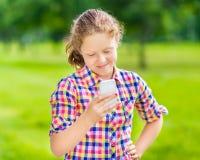 有智能手机的微笑的少年女孩 免版税库存照片