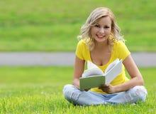 读书的女孩。有书的愉快的白肤金发的美丽的少妇坐草。室外 免版税库存图片