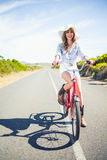 微笑的俏丽式样摆在,当骑自行车时 图库摄影