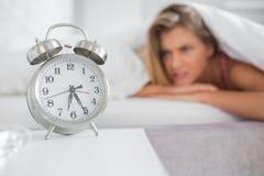 Ενοχλημένο ξανθό να κοιτάξει επίμονα στο ξυπνητήρι της Στοκ Φωτογραφίες