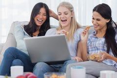 一起看膝上型计算机和吃的笑的朋友曲奇饼 库存图片