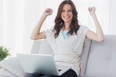 有膝上型计算机的欢呼的妇女在她的膝盖 库存图片
