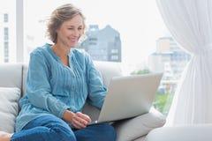 快乐的白肤金发的妇女坐她的长沙发使用膝上型计算机 免版税图库摄影